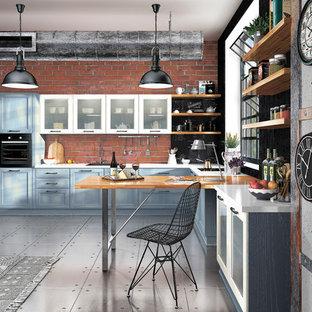 モスクワの大きいインダストリアルスタイルのおしゃれなキッチン (ドロップインシンク、シェーカースタイル扉のキャビネット、青いキャビネット、木材カウンター、茶色いキッチンパネル、レンガのキッチンパネル、カラー調理設備、セラミックタイルの床) の写真