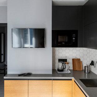Источник вдохновения для домашнего уюта: угловая кухня среднего размера в современном стиле с врезной раковиной, плоскими фасадами, светлыми деревянными фасадами, белым фартуком, фартуком из керамогранитной плитки, черной техникой, полом из керамогранита, серым полом и серой столешницей