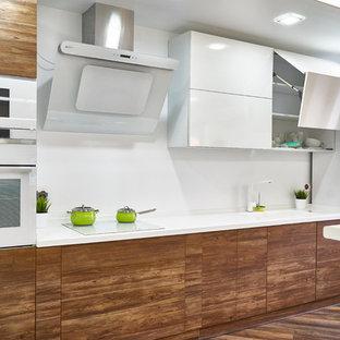 Пример оригинального дизайна: линейная кухня в современном стиле с накладной раковиной, плоскими фасадами, фасадами цвета дерева среднего тона, белым фартуком, белой техникой, белой столешницей и паркетным полом среднего тона