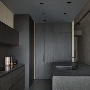 Medium sized contemporary l-shaped open plan kitchen in Moscow with an integrated sink, flat-panel cabinets, black cabinets, granite worktops, black splashback, stone slab splashback, black appliances, concrete flooring, an island, blue floors and black worktops.