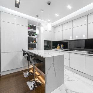 Пример оригинального дизайна: отдельная кухня среднего размера в современном стиле с плоскими фасадами, белыми фасадами, черным фартуком, фартуком из стекла, полуостровом, белым полом и накладной раковиной