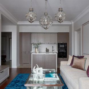 Пример оригинального дизайна: линейная кухня-гостиная в стиле современная классика с фасадами с утопленной филенкой, бежевыми фасадами, белым фартуком, черной техникой, островом и белой столешницей