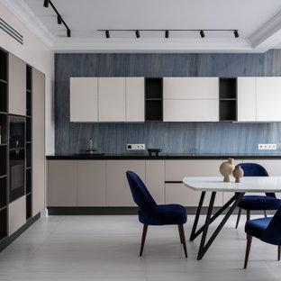 モスクワのトランジショナルスタイルのおしゃれなキッチン (フラットパネル扉のキャビネット、グレーのキャビネット、青いキッチンパネル、黒い調理設備、アイランドなし、白い床、黒いキッチンカウンター、折り上げ天井) の写真
