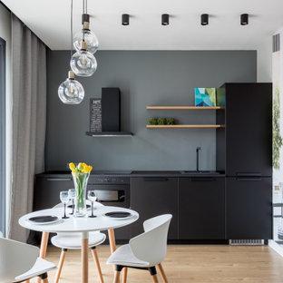 Стильный дизайн: маленькая прямая кухня в современном стиле с обеденным столом, накладной раковиной, плоскими фасадами, черными фасадами, черной техникой, паркетным полом среднего тона, коричневым полом, черной столешницей и серым фартуком без острова - последний тренд