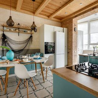 Неиссякаемый источник вдохновения для домашнего уюта: п-образная кухня в морском стиле с обеденным столом, накладной раковиной, фасадами с утопленной филенкой, бирюзовыми фасадами, столешницей из дерева, белой техникой, полуостровом, разноцветным полом и коричневой столешницей