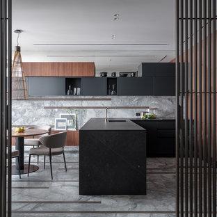 Идея дизайна: п-образная кухня в современном стиле с плоскими фасадами, черными фасадами, серым фартуком, фартуком из каменной плиты, полуостровом, серым полом, черной столешницей, обеденным столом и врезной раковиной