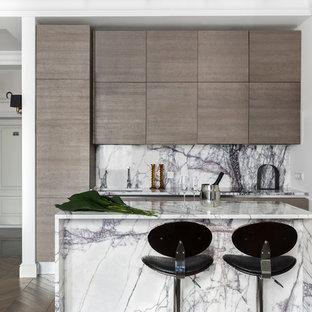 На фото: параллельная кухня в современном стиле с плоскими фасадами, фасадами цвета дерева среднего тона, мраморной столешницей, белым фартуком, фартуком из мрамора, паркетным полом среднего тона, островом, коричневым полом и белой столешницей