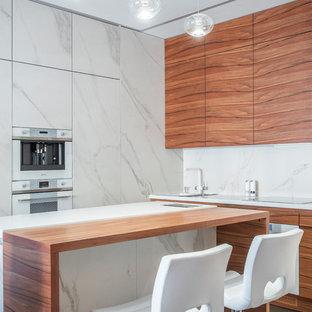 На фото: угловая кухня в современном стиле с плоскими фасадами, фасадами цвета дерева среднего тона, белым фартуком, белой техникой, островом, серым полом и белой столешницей