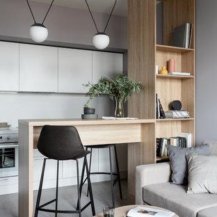 Идея дизайна: кухня-гостиная среднего размера в скандинавском стиле с плоскими фасадами, белыми фасадами, белым фартуком, белой техникой, светлым паркетным полом и полуостровом