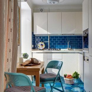 Новые идеи обустройства дома: маленькая угловая кухня-гостиная в современном стиле с монолитной раковиной, плоскими фасадами, белыми фасадами, столешницей из кварцевого композита, синим фартуком, фартуком из керамической плитки, техникой из нержавеющей стали и полом из керамической плитки без острова