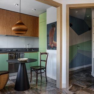 Выдающиеся фото от архитекторов и дизайнеров интерьера: кухня в современном стиле с обеденным столом, плоскими фасадами, зелеными фасадами, техникой из нержавеющей стали, коричневым полом, черной столешницей, врезной раковиной, серым фартуком и фартуком из стекла