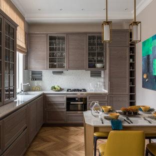 Пример оригинального дизайна: угловая кухня в стиле современная классика с врезной раковиной, фасадами с утопленной филенкой, фасадами цвета дерева среднего тона, белым фартуком, техникой из нержавеющей стали, паркетным полом среднего тона, коричневым полом, белой столешницей и обеденным столом без острова