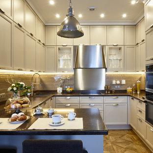Пример оригинального дизайна интерьера: большая п-образная кухня-гостиная в стиле современная классика с врезной раковиной, фасадами с утопленной филенкой, серыми фасадами, столешницей из кварцевого композита, бежевым фартуком, фартуком из керамической плитки, техникой из нержавеющей стали, полом из керамической плитки, полуостровом и коричневым полом
