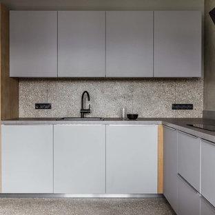 Diseño de cocina en L, actual, con armarios con paneles lisos, puertas de armario grises, salpicadero verde, suelo de terrazo, suelo gris y encimeras grises