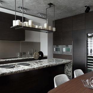 На фото: большая параллельная кухня-гостиная в современном стиле с врезной раковиной, плоскими фасадами, темными деревянными фасадами, столешницей из гранита, фартуком из стекла, островом, серым фартуком, техникой из нержавеющей стали и серой столешницей с