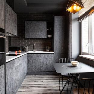 На фото: угловая кухня в современном стиле с обеденным столом, монолитной раковиной, плоскими фасадами, серыми фасадами, серым фартуком, техникой из нержавеющей стали, паркетным полом среднего тона, коричневым полом и белой столешницей с