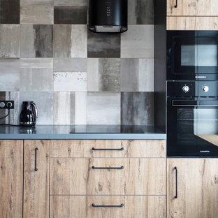 Свежая идея для дизайна: кухня в стиле лофт с плоскими фасадами, светлыми деревянными фасадами, серым фартуком, черной техникой, серым полом и серой столешницей - отличное фото интерьера