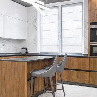 Выдающиеся фото от архитекторов и дизайнеров интерьера: п-образная кухня-гостиная в современном стиле с плоскими фасадами, белым фартуком, фартуком из каменной плитки, черной техникой, мраморным полом и островом