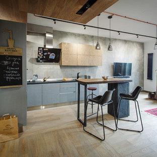 Свежая идея для дизайна: угловая кухня-гостиная в стиле лофт с плоскими фасадами, серыми фасадами, серым фартуком, светлым паркетным полом и островом - отличное фото интерьера