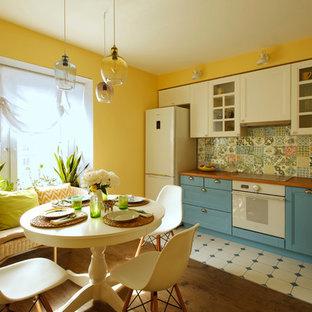 Свежая идея для дизайна: угловая кухня среднего размера в классическом стиле с обеденным столом, фасадами с утопленной филенкой, белыми фасадами, разноцветным фартуком, фартуком из керамогранитной плитки, накладной раковиной и белой техникой без острова - отличное фото интерьера