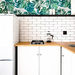 Новый формат декора квартиры: маленькая угловая кухня в современном стиле с обеденным столом, накладной раковиной, столешницей из дерева, белым фартуком, фартуком из плитки кабанчик, техникой из нержавеющей стали, плоскими фасадами, белыми фасадами и коричневой столешницей