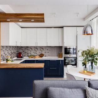 Неиссякаемый источник вдохновения для домашнего уюта: п-образная кухня в стиле современная классика с обеденным столом, врезной раковиной, фасадами в стиле шейкер, синими фасадами, столешницей из дерева, серым фартуком, белой техникой, полуостровом, бежевым полом и коричневой столешницей