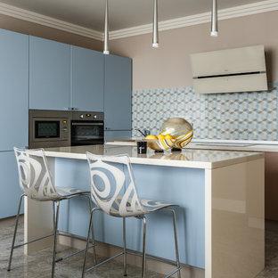 Свежая идея для дизайна: кухня среднего размера в современном стиле с плоскими фасадами, синими фасадами, техникой из нержавеющей стали, островом, серым полом и разноцветным фартуком - отличное фото интерьера