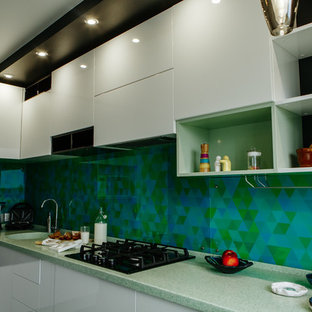 Mid-sized contemporary l-shaped separate kitchen in Other with an integrated sink, flat-panel cabinets, white cabinets, solid surface benchtops, green splashback, glass tile splashback, stainless steel appliances, laminate floors, no island, black floor and turquoise benchtop.