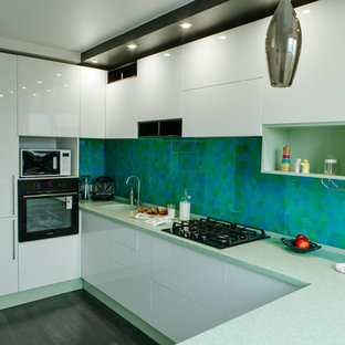 Design ideas for a mid-sized contemporary l-shaped separate kitchen in Other with an integrated sink, flat-panel cabinets, white cabinets, solid surface benchtops, green splashback, glass tile splashback, stainless steel appliances, laminate floors, no island, black floor and turquoise benchtop.