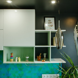 Inspiration for a mid-sized contemporary l-shaped separate kitchen in Other with an integrated sink, flat-panel cabinets, white cabinets, solid surface benchtops, green splashback, glass tile splashback, stainless steel appliances, laminate floors, no island, black floor and turquoise benchtop.
