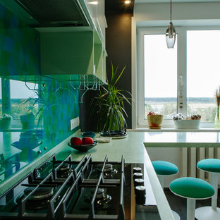 This is an example of a mid-sized contemporary l-shaped separate kitchen in Other with an integrated sink, flat-panel cabinets, white cabinets, solid surface benchtops, green splashback, glass tile splashback, stainless steel appliances, laminate floors, no island, black floor and turquoise benchtop.