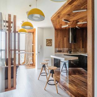 На фото: п-образные кухни-гостиные в современном стиле с плоскими фасадами, черными фасадами, коричневым фартуком, черной техникой, темным паркетным полом, полуостровом, коричневым полом и фартуком из дерева