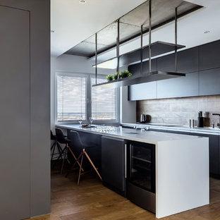 Стильный дизайн: линейная кухня в современном стиле с плоскими фасадами, черными фасадами, коричневым фартуком, островом, коричневым полом и белой столешницей - последний тренд