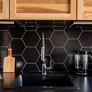 サンクトペテルブルクの小さいコンテンポラリースタイルのおしゃれなキッチン (ドロップインシンク、落し込みパネル扉のキャビネット、中間色木目調キャビネット、大理石カウンター、黒いキッチンパネル、塗装板のキッチンパネル、白い調理設備、磁器タイルの床、ベージュの床、黒いキッチンカウンター) の写真