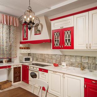 他の地域の中サイズの地中海スタイルのおしゃれなキッチン (一体型シンク、インセット扉のキャビネット、赤いキャビネット、人工大理石カウンター、茶色いキッチンパネル、セラミックタイルのキッチンパネル、白い調理設備、淡色無垢フローリング、アイランドなし) の写真