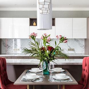 На фото: линейная кухня-гостиная среднего размера в современном стиле с плоскими фасадами, коричневыми фасадами, белым фартуком, черной техникой, островом и белой столешницей с