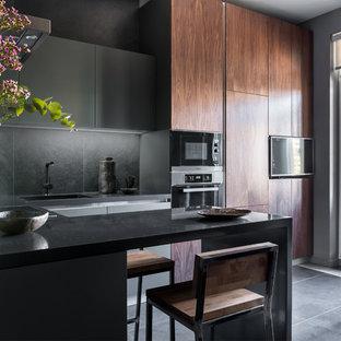 Идея дизайна: маленькая угловая кухня-гостиная в современном стиле с плоскими фасадами, серыми фасадами, столешницей из акрилового камня, серым фартуком, фартуком из керамогранитной плитки, техникой из нержавеющей стали, полом из керамогранита, полуостровом, черным полом и черной столешницей