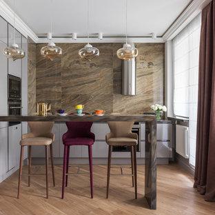 Пример оригинального дизайна: угловая кухня-гостиная в стиле современная классика с плоскими фасадами, серыми фасадами, коричневым фартуком, техникой из нержавеющей стали, паркетным полом среднего тона и коричневым полом