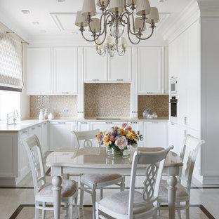Стильный дизайн: п-образная кухня в классическом стиле с обеденным столом, фасадами с утопленной филенкой, белыми фасадами, белой техникой, белым полом и бежевой столешницей - последний тренд
