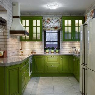 Пример оригинального дизайна интерьера: п-образная кухня-гостиная среднего размера в стиле кантри с фасадами с выступающей филенкой, зелеными фасадами, бежевым фартуком, белой техникой, врезной раковиной, столешницей из акрилового камня, фартуком из керамической плитки, полом из керамической плитки, бежевым полом и серой столешницей без острова