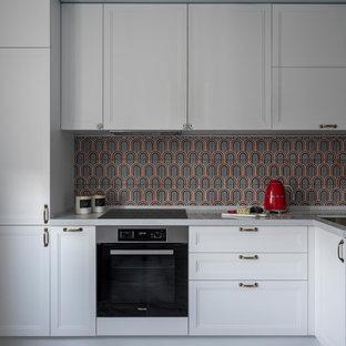 Идея дизайна: отдельная, угловая кухня в современном стиле с врезной раковиной, фасадами с утопленной филенкой, белыми фасадами, разноцветным фартуком, техникой из нержавеющей стали, серым полом и серой столешницей