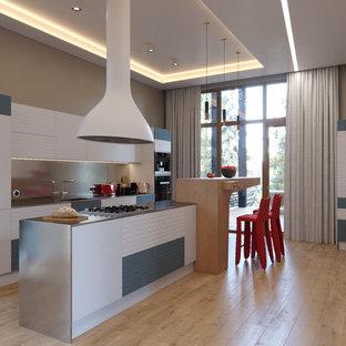 Свежая идея для дизайна: параллельная кухня в современном стиле с обеденным столом, раковиной в стиле кантри, плоскими фасадами, белыми фасадами, столешницей из нержавеющей стали, фартуком цвета металлик, техникой из нержавеющей стали, светлым паркетным полом, островом и бежевым полом - отличное фото интерьера