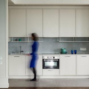 Свежая идея для дизайна: кухня в современном стиле с фасадами с декоративным кантом, белыми фасадами, серым фартуком, техникой из нержавеющей стали, серым полом и серой столешницей без острова - отличное фото интерьера