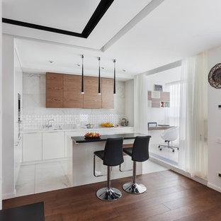 На фото: угловая кухня-гостиная среднего размера в современном стиле с двойной раковиной, плоскими фасадами, белыми фасадами, столешницей из акрилового камня, белым фартуком, фартуком из керамогранитной плитки, белой техникой, островом и белой столешницей