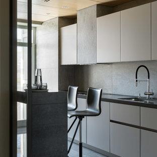 Удачное сочетание для дизайна помещения: большая линейная кухня-гостиная в скандинавском стиле с врезной раковиной, плоскими фасадами, серыми фасадами, серым фартуком, серым полом и черной столешницей без острова - самое интересное для вас