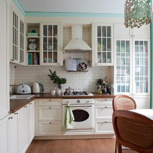 На фото: отдельные, угловые кухни в стиле современная классика с накладной раковиной, фасадами с утопленной филенкой, белыми фасадами, белым фартуком, фартуком из плитки кабанчик, белой техникой и коричневым полом без острова