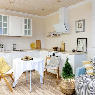 Пример оригинального дизайна: маленькая угловая кухня-гостиная в скандинавском стиле с накладной раковиной, фасадами с выступающей филенкой, белыми фасадами, белой техникой, бежевым полом, бежевой столешницей и полом из ламината