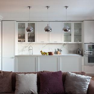 На фото: параллельная кухня-гостиная в скандинавском стиле с фасадами с утопленной филенкой, белыми фасадами, белым фартуком, фартуком из каменной плиты, техникой под мебельный фасад, паркетным полом среднего тона, островом, коричневым полом и белой столешницей с