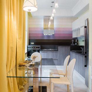 Свежая идея для дизайна: угловая кухня-гостиная в современном стиле с накладной раковиной, плоскими фасадами, темными деревянными фасадами, черным фартуком и черной техникой без острова - отличное фото интерьера