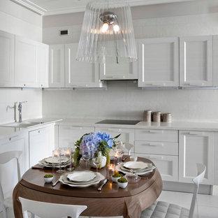 На фото: кухня - столовая в стиле современная классика с накладной раковиной, белыми фасадами, белым фартуком, фасадами в стиле шейкер и белой техникой с